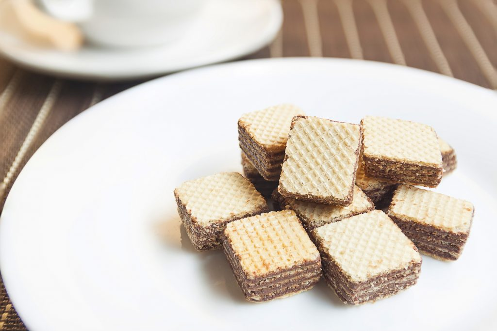 Wafers cubes with chocolate. on White plate